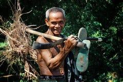 ηλικιωμένο ανώτερο khmer άτομο που περπατά κατ' οίκον από το αγρόκτημά του με μερικές ρίζες και το εργαλείο του στο χέρι του στοκ φωτογραφίες