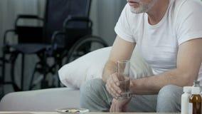 Ηλικιωμένο αρσενικό παίρνοντας χάπι, που εξετάζει την αναπηρική καρέκλα που στέκεται στο υπόβαθρο, τραύμα απόθεμα βίντεο