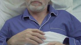 Ηλικιωμένο αρσενικό που βρίσκεται στο κρεβάτι και τον ύπνο, που αναπνέουν ήρεμα, ανενόχλητος ύπνος απόθεμα βίντεο