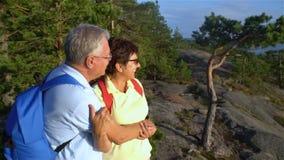 Ηλικιωμένο ενεργό ζεύγος που αναρριχείται στο βράχο και που θαυμάζει την ανατολή, το ηλιοβασίλεμα φιλμ μικρού μήκους