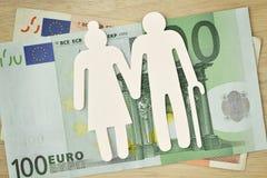 Ηλικιωμένο ζεύγος εγγράφου που αποκόπτει στα ευρο- τραπεζογραμμάτια - συνταξιοδοτική έννοια στοκ φωτογραφίες