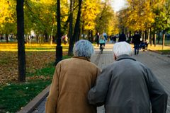 Ηλικιωμένο ζεύγος που περπατά στο πάρκο την ημέρα φθινοπώρου στοκ εικόνες