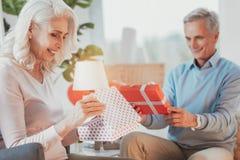 Ηλικιωμένο θετικό ζεύγος τα δώρα ανοίγματός τους στοκ εικόνες