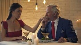 Ηλικιωμένο χέρι φιλήματος ατόμων της νέας συζύγου, ρομαντική ημερομηνία στο εστιατόριο απόθεμα βίντεο