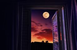 Ηλιοβασίλεμα και ανατολή του φεγγαριού που βλέπουν από ένα ανοικτό παράθυρο στοκ εικόνες με δικαίωμα ελεύθερης χρήσης