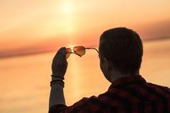Ηλιοβασίλεμα μέσω των γυαλιών ηλίου στα αρσενικά χέρια Στοκ φωτογραφίες με δικαίωμα ελεύθερης χρήσης
