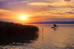 Ηλιοβασίλεμα με τις σκιαγραφίες στη λίμνη Balaton στην Ουγγαρία Στοκ Εικόνες