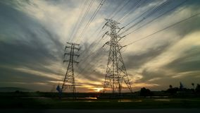 Ηλιοβασίλεμα με τον πύργο ηλεκτροφόρων καλωδίων δύο μετάδοσης στον τομέα ορυζώνα απόθεμα βίντεο