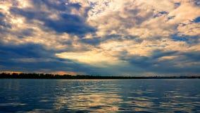ηλιοβασίλεμα μπροστά από μια καταιγίδα, στον ορίζοντα του ποταμού στοκ φωτογραφίες