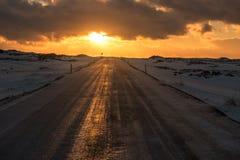 Ηλιοβασίλεμα πέρα από έναν παγωμένο δρόμο στην Ισλανδία Στοκ Φωτογραφία