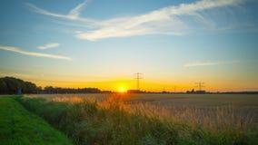 Ηλιοβασίλεμα πέρα από έναν τομέα με ένα ηλεκτροφόρο καλώδιο, χρόνος-σφάλμα απόθεμα βίντεο
