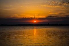 Ηλιοβασίλεμα πέρα από μια λίμνη μια νεφελώδη ημέρα Στοκ Εικόνα