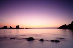 Ηλιοβασίλεμα πέρα από τη θάλασσα Cantabric στη σιωπηλή παραλία Στοκ Εικόνες