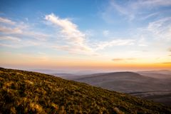 Ηλιοβασίλεμα πέρα από τον ανεμιστήρα μανδρών Υ, σειρά βουνών, Ουαλία UK Στοκ Φωτογραφίες