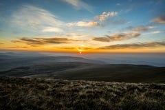 Ηλιοβασίλεμα πέρα από τον ανεμιστήρα μανδρών Υ, σειρά βουνών, Ουαλία UK στοκ εικόνα