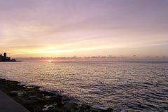 Ηλιοβασίλεμα πέρα από τον Ατλαντικό Ωκεανό με το κατοικημένο κτήριο στο υπόβαθρο - Αβάνα, Κούβα Στοκ Εικόνα