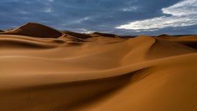 Ηλιοβασίλεμα πέρα από τους αμμόλοφους άμμου στην έρημο