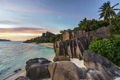 Ηλιοβασίλεμα πέρα από τους βράχους, άμμος, φοίνικες, τυρκουάζ νερό στην τροπική παραλία, λ Στοκ Φωτογραφίες