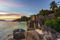 Ηλιοβασίλεμα πέρα από τους βράχους, άμμος, φοίνικες, τυρκουάζ νερό στην τροπική παραλία, λ Στοκ Φωτογραφία