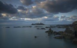 Ηλιοβασίλεμα πέρα από το φάρο Godrevy στο νησί Godrevy στον κόλπο του ST Ives με την παραλία και τους βράχους στο πρώτο πλάνο, Κο στοκ φωτογραφία με δικαίωμα ελεύθερης χρήσης