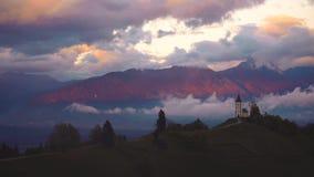 Ηλιοβασίλεμα πέρα από Jamnik, Σλοβενία Εναέρια άποψη κηφήνων πέρα από τις Άλπεις και την εκκλησία ST Primoz φιλμ μικρού μήκους