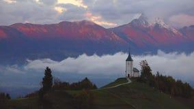 Ηλιοβασίλεμα πέρα από Jamnik, Σλοβενία Ουράνιο τόξο, Άλπεις και εκκλησία του ST Primoz, εναέρια άποψη κηφήνων απόθεμα βίντεο
