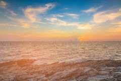 Ηλιοβασίλεμα πέρα από seacoast τον ορίζοντα με το βράχο στην παραλία Στοκ Εικόνα