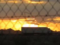 Ηλιοβασίλεμα πίσω από τα δέντρα με τα σύννεφα και έναν δρόμο στο πρώτο πλάνο στοκ εικόνες