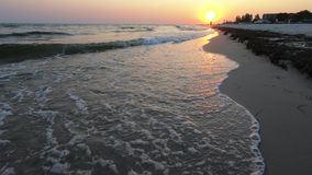 Ηλιοβασίλεμα παραλιών με τον πορτοκαλή ήλιο και τα foamy κύματα απόθεμα βίντεο