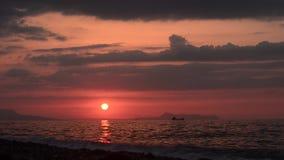 Ηλιοβασίλεμα που αγνοεί το βουνό και τη βάρκα στην ακτή απόθεμα βίντεο