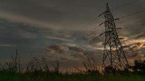 Ηλιοβασίλεμα που συλλαμβάνεται νεφελώδες με τον πύργο στο πρώτο πλάνο στοκ εικόνες