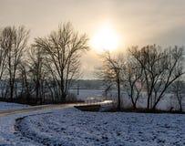 Ηλιοβασίλεμα σε έναν χιονώδη τομέα με έναν δρόμο και μερικά δέντρα στα ευρωπαϊκά όρη μια κρύα ημέρα το χειμώνα στοκ εικόνες