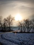 Ηλιοβασίλεμα σε έναν χιονώδη τομέα με έναν δρόμο και μερικά δέντρα στα ευρωπαϊκά όρη μια κρύα ημέρα το χειμώνα στοκ εικόνες με δικαίωμα ελεύθερης χρήσης