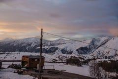 Ηλιοβασίλεμα στα βουνά Kaukaz με τη σιταποθήκη στο χειμώνα στοκ φωτογραφία