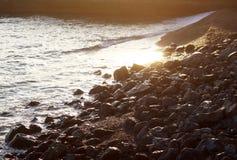 Ηλιοβασίλεμα στην ακτή Κριμαία Μαύρης Θάλασσας Οι θερμές ακτίνες του ήλιου φωτίζουν την ακτή στοκ εικόνα