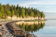 Ηλιοβασίλεμα στην παραλία Απότομος βράχος ασβεστόλιθων στη θάλασσα κάτω από το μπλε ουρανό και τα άσπρα σύννεφα Στοκ εικόνα με δικαίωμα ελεύθερης χρήσης