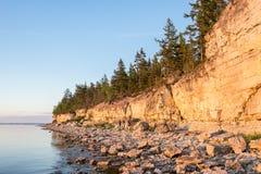 Ηλιοβασίλεμα στην παραλία Απότομος βράχος ασβεστόλιθων στη θάλασσα κάτω από το μπλε ουρανό και τα άσπρα σύννεφα Στοκ εικόνες με δικαίωμα ελεύθερης χρήσης