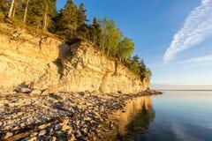 Ηλιοβασίλεμα στην παραλία Απότομος βράχος ασβεστόλιθων στη θάλασσα κάτω από το μπλε ουρανό και τα άσπρα σύννεφα Στοκ Φωτογραφία