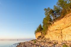 Ηλιοβασίλεμα στην παραλία Απότομος βράχος ασβεστόλιθων στη θάλασσα κάτω από το μπλε ουρανό και τα άσπρα σύννεφα Στοκ Εικόνα