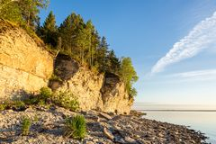 Ηλιοβασίλεμα στην παραλία Απότομος βράχος ασβεστόλιθων στη θάλασσα κάτω από το μπλε ουρανό και τα άσπρα σύννεφα Στοκ Εικόνες