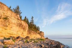 Ηλιοβασίλεμα στην παραλία Απότομος βράχος ασβεστόλιθων στη θάλασσα κάτω από το μπλε ουρανό και τα άσπρα σύννεφα Στοκ Φωτογραφίες
