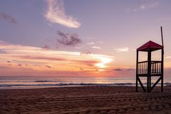 Ηλιοβασίλεμα στην παραλία δίπλα στο καταφύγιο lifeguard Αφίσα που δείχνει το καταφύγιο στα ιταλικά στοκ φωτογραφίες