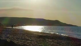 Ηλιοβασίλεμα στην παραλία θάλασσας απόθεμα βίντεο