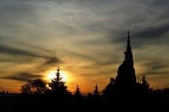 Ηλιοβασίλεμα στην πόλη, με τα σκοτεινά δέντρα και μια εκκλησία στοκ φωτογραφίες
