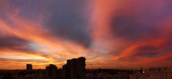 Ηλιοβασίλεμα στην πόλη με τη ζάλη των ζωηρόχρωμων μαγικών σύννεφων Ουρανός άνοιξη με την κόκκινη άποψη σύννεφων και στεγών Στοκ Φωτογραφία