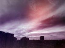 Ηλιοβασίλεμα στην πόλη με τη ζάλη των ζωηρόχρωμων μαγικών σύννεφων Ουρανός άνοιξη με την κόκκινη άποψη σύννεφων και στεγών Στοκ Εικόνες