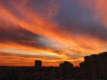 Ηλιοβασίλεμα στην πόλη με τη ζάλη των ζωηρόχρωμων μαγικών σύννεφων Ουρανός άνοιξη με την κόκκινη άποψη σύννεφων και στεγών Στοκ φωτογραφίες με δικαίωμα ελεύθερης χρήσης