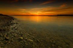Ηλιοβασίλεμα στη δύσκολη παραλία εν πλω στοκ φωτογραφία