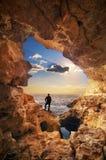 Ηλιοβασίλεμα στη σκιαγραφία grotto και ατόμων Στοκ εικόνα με δικαίωμα ελεύθερης χρήσης