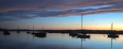 Ηλιοβασίλεμα στο λυκόφως πέρα από τις λιμενικές βάρκες κόλπων Morro και το βράχο Morro στην κεντρική ακτή Καλιφόρνιας σε Καλιφόρν στοκ εικόνα